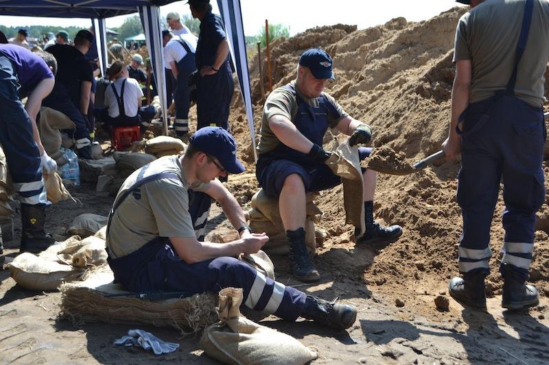 Die Sandsäcke müssen mit Sand befüllt und anschließend verschlossen werden.