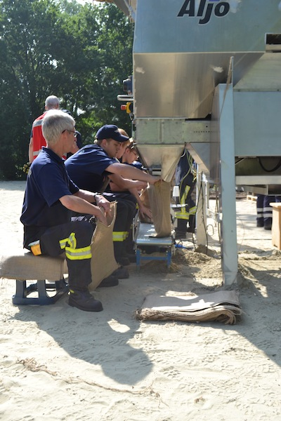 An den Sandsackfüllmaschinen werden die Sandsäcke automatisch befüllt und verschlossen.