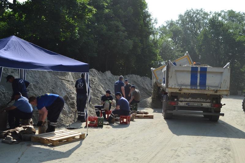 Füllen der Sandsäcke mit Hand, im Hintergrund wird neuer Sand angeliefert.